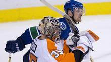 Vancouver Canucks left wing Daniel Sedin (22) watches the replay on the jumbotron as Philadelphia Flyers goalie Steve Mason (35) celebrates his teams win following a shootout during NHL action in Vancouver, B.C. Monday, Dec. 30, 2013. (JONATHAN HAYWARD/THE CANADIAN PRESS)