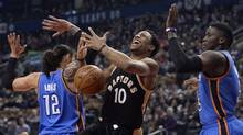 Raptors guard DeMar DeRozan gets blocked by Oklahoma City Thunder centre Steven Adams (12) and guard Victor Oladipo (5) during first half NBA basketball action, in Toronto on March 16, 2017. (Nathan Denette/THE CANADIAN PRESS)