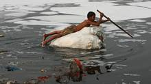 A boy looks for recyclable items in the polluted waters of the Yamuna river in New Delhi in this 2009 photo. (RUPAK DE CHOWDHURI/RUPAK DE CHOWDHURI/REUTERS)