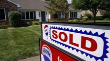 A sold sign is posted outside a home in Springfield, Ill., in this file photo. (Seth Perlman/AP)