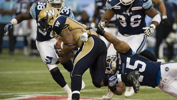 Winnipeg Blue Bombers Chad Simpson is tackled by Toronto Argonauts Robert McCune during first half CFL action in Toronto on Wednesday, July 18, 2012. (Aaron Vincent Elkaim/THE CANADIAN PRESS)