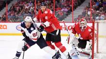 Team Canada's Jay Bouwmeester, middle, pushes Team USA's Justin Abdelkader as Canada goaltender Braden Holtby looks on from the net during first period pre-tournament World Cup of Hockey action in Ottawa on Saturday, Sept. 10, 2016. (Sean Kilpatrick/THE CANADIAN PRESS)