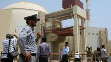"An Iranian security man stands next to journalists outside the reactor building at the Russian-built Bushehr nuclear power plant in southern Iran on August 21, 2010. The Stuxnet computer worm has infected 30,000 computers in Iran but has failed to ""cause serious damage, "" Iranian officials were quoted as saying on September 26, 2010. (ATTA KENARE/AFP)"
