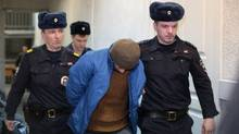Guards escort a suspect into a court hearing in St. Petersburg, Russia, Thursday, April 6, 2017. (Yevgeny Kurskov/AP)