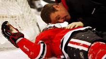 Chicago Blackhawks' Brian Campbell, left, talks to a team trainer after being knocked down by Washington Capitals' Alex Ovechkin during the first period of an NHL hockey game in Chicago, Sunday. (Nam Y. Huh/Nam Y. Huh/AP)