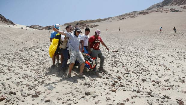 Medics, helped of fans, evacuate Leonardo Martinez of Bolivia who was injured after crashing with his quad in the third stage of the 2013 Dakar Rally from Pisco to Nazca, Peru, Monday, Jan. 7, 2013. (Victor R. Caivano/AP Photo)