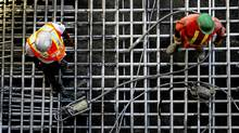 Workers stand on the foundation at a condominium construction project in Toronto, Ontario, Canada, on Monday, July 18, 2011. This week will bring reports on housing starts, building permits and the house price index. (Brent Lewin/Bloomberg/Brent Lewin/Bloomberg)