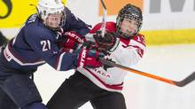 Canada's Caroline Quellette, right, takes a hit from USA's Hilary Knight during pre-Olympic women's hockey action in Calgary, Alta., Thursday, December 12, 2013. (Larry MacDougal/THE CANADIAN PRESS)