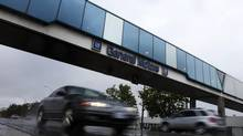 Cars pass under an overpass at the General Motors assembly plant in Oshawa, Ont. GM officials have refused to promise that equivalent production of Camaro vehicles currently assembled in Oshawa will be replaced. (MARK BLINCH/REUTERS)