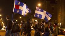 Students hold flags during a march to protest against tuition hikes in downtown Montreal, Quebec April 28, 2012. (CHRISTINNE MUSCHI/REUTERS/CHRISTINNE MUSCHI/REUTERS)