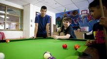 Jacky Mah, left, day program leader, plays with kids at the Strathcona Community Centre in Vancouver on Monday. (Ben Nelms for The Globe and Mail)