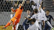 Los Angeles Galaxy's Edson Buddle, top left, attempts to score against Vancouver Whitecaps goalkeeper Brad Knighton, left, in the first half of an MLS playoff match in Carson, Calif., Thursday, Nov. 1, 2012. (Jae C. Hong/AP)