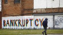 A man walk past graffiti in Detroit, Michigan in this file photo taken December 3, 2013. (JOSHUA LOTT/REUTERS)
