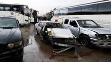 Damaged vehicles are pictured at the site of an attack by two suicide bombers in Damascus, Syria, on March 11, 2017. (OMAR SANADIKI/REUTERS)