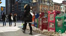 A woman walks by newspaper stands in downtown Toronto on Friday, Feb. 20, 2015. (Galit Rodan For The Globe and Mail)