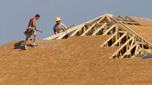 Carpenters work to enclose a roof on a home being built in Sprinfield, Ill. (Seth Perlman/AP)