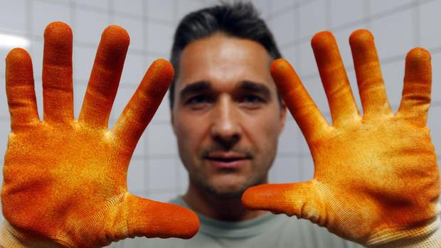 Paprika maker Peter Szabo shows his pepper-stained gloves in Batya, 140 kilometres south of Budapest. Mr. Szabo, 41, left a lucrative telecommunications job in Britain, sold his property and returned to Batya to grow red peppers. (LASZLO BALOGH/REUTERS)