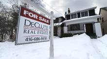 A realtor's 'Sold' sign stands outside a home in Toronto, March 5, 2014. (Fred Lum/The Globe and Mail)