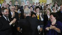 NDP Leader Jack Layton is hugged by his wife and MP Olivia Chow as he is applauded by his new caucus following a speech on Parliament Hill in Ottawa on May 24, 2011. (Sean Kilpatrick/The Canadian Press)