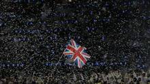 Confetti rains down as Britain's flag bearer Chris Hoy holds the national flag as he leads the contingent in the athletes parade during the opening ceremony of the London 2012 Olympic Games at the Olympic Stadium. (PHIL NOBLE/REUTERS)