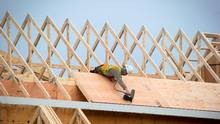 A construction worker nails down plywood on the roof of a townhouse under construction at the site of the former Steveston Secondary School in Richmond, B.C., on Friday, Jan. 8, 2016. The school was closed in 2007. (DARRYL DYCK FOR THE GLOBE AND MAIL)