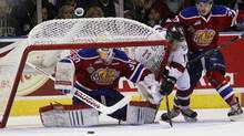 Edmonton Oil Kings goalie Tristan Jarry watches the puck as Guelph Storm's Jason Dickinson is checked into the net by Dysin Mayo, upsetting the net over onto Jarry during second period Memorial Cup action in London on May 17. (Dave Chidley/THE CANADIAN PRESS)