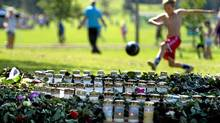 A Norway cup soccer player warms next to a makeshift memorial alongside the football pitches for the victims on government buildings and massacre on the youth camp of the Norwegian Labour Party in Oslo on July 31, 2011. (Odd Andersen/AFP/Getty Images/Odd Andersen/AFP/Getty Images)