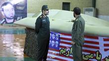 A file photo released Dec. 8, 2011, by the Iranian Revolutionary Guards, claims to show the chief of the aerospace division of Iran's Revolutionary Guards, Gen. Amir Ali Hajizadeh, left, listening to an unidentified colonel as he points to a U.S. RQ-170 Sentinel drone which Tehran says its forces downed. (Sepahnews/AP)