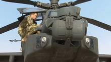 In this image from video, Britain's Prince Harry is shown an Apache helicopter by a member of his squadron, obscured behind, (name not provided) at Camp Bastion in Afghanistan, Friday Sept. 7, 2012 (AP/TV Pool)
