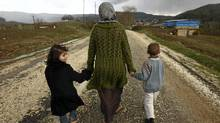 Sawssan Abdelwahab, who fled Idlib in Syria, walks with her children outside the refugees camp near the Turkish-Syrian border in the southeastern city of Yayladagi Feb. 16, 2012. (ZOHRA BENSEMRA/ZOHRA BENSEMRA/REUTERS)