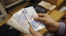 A money changer counts Turkish lira bills at a currency exchange office in central Istanbul January 29, 2014. (MURAD SEZER/REUTERS)