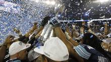 Toronto Argonauts players hold the CFL Grey Cup after defeating Calgary Stampeders Sunday November 25, 2012 in Toronto. (Peter Power/The Globe and Mail)