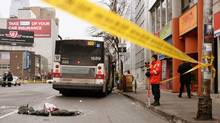 Two Toronto police officers survey the scene Jan. 18 after a woman was struck and killed by a TTC bus at Mount Pleasant Road and Eglington Avenue. Tragedies such as this have touched off a debate about road safety in Toronto and the GTA. (DAVE CHAN/Dave Chan for The Globe and Mail)
