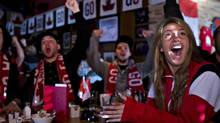 Fans react to Canada's 3-0 victory over Sweden in men's hockey gold medal finals at the Olympics while watching at a sports bar in L'Ancienne Lorette, Que., on Sunday, February 23, 2014. (Jacques Boissinot/THE CANADIAN PRESS)