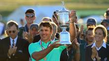 Brooks Koepka poses with the winner's trophy after his victory at the U.S. Open at Erin Hills on Sunday. (Richard Heathcote/Getty Images)