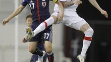 Japan's Makoto Hasebe fights for the ball with Canada's Marcus Haber during their international friendly soccer match in Doha March 22, 2013. (MOHAMMED DABBOUS/REUTERS)