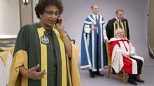 Indira Samarasekera, president of the University of Alberta, talks on the phone during a photo session with participants in a convocation ceremony in Edmonton on Wednesday. (JASON FRANSON FOR THE GLOBE AND MAIL)