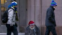 Pedestrians pass a homeless man begging in front of the Design Exchange on Bay Street in downtown Toronto on Dec. 16, 2013. (Peter Power/The Globe and Mail) (Peter Power/The Globe and Mail)