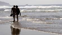 In this Aug. 26, 2010 file photo, a couple walks through the surf together in Cannon Beach, Ore. (Don Ryan/AP)