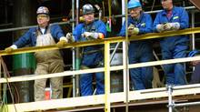 Workers st Suncor's Fort McMurray oil sands processing plant take a break during construction work. (JEFF McINTOSH/GLOBE AND MAIL)