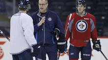 Paul Maurice, the new head coach of the Winnipeg Jets, talks with Bryan Little (18) during his first practice in Winnipeg on Monday, January 13, 2014. (JOHN WOODS/THE CANADIAN PRESS)