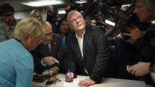 Councillor Doug Ford looks up at the hovering tv cameras while signing his nomination papers at the city hall's Elections Services office on Sept. 12. (Fred Lum/The Globe and Mail)