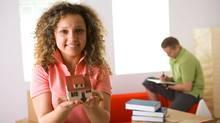 Smiling woman holding miniature house (Jupiterimages/(c) Jupiterimages)