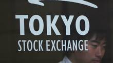 A man is seen behind a logo of the Tokyo Stock Exchange (TSE) as he walks out from the bourse in Tokyo July 6, 2011. (Yuriko Nakao/Reuters/Yuriko Nakao/Reuters)