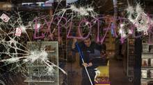 A worker cleans a shop stormed by demostrators following clashes between police and protesters after an anti-austerity general strike in Barcelona, Spain, Friday, March 30, 2012. (Emilio Morenatti/Emilio Morenatti/AP)