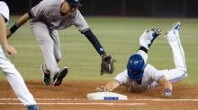 New York Yankees shortstop Derek Jeter is unable to tag out Colby Rasmus of the Toronto Blue Jays during the fifth inning at Rogers Centre on Tuesday. (Nick Turchiaro/USA Today Sports)