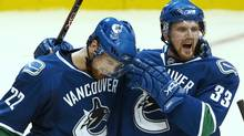 Vancouver Canucks' Daniel Sedin, left, is congratulated by his twin brother Henrik Sedin after Daniel scored against the Dallas Stars during the third period of their NHL hockey game in Vancouver, British Columbia December 20, 2007. (ANDY CLARK/Reuters)