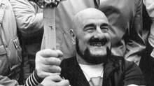 Maurice (Mad Dog) Vachon gets the Olympic Torch during the run through downtown Montreal here December 12, 1987. (REUTERS)