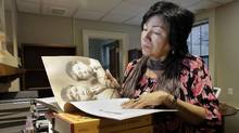 Rose Hart, a residential school survivor and community engagement officer for the Truth and Reconciliation Commission of Canada, leafs through books in the library of the National Centre for Truth and Reconciliation in Winnipeg on Dec. 21, 2015. (LYLE STAFFORD/GLOBE AND MAIL)