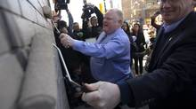 Mayor Rob Ford, left, and councillor Gary Crawford paint over some graffiti on the outside of a Pizza Pizza location at Kingston Rd. and Victoria Park Ave. in Toronto, Ont. Wednesday, April 17, 2013. (Kevin Van Paassen/The Globe and Mail)